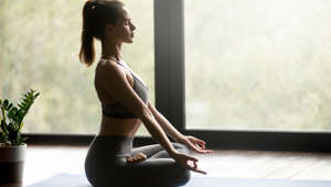 Young sporty attractive woman practicing yoga, doing Ardha Padmasana exercise, Half Lotus pose with mudra, working out, wearing sportswear, grey pants, top, indoor full length, yoga studio, side view