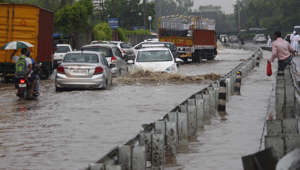 GURUGRAM, INDIA - JULY 18: Vehicles wade through a waterlogged road after heavy rain, on July 18, 2019 in Gurugram, India. All parts of Delhi received rain in the past 24 hours. Early morning showers slowed down vehicular traffic on many stretches with waterlogging reported from some low lying areas. Maximum temperature is expected to be around 31 degrees Celsius. The city recorded a high of 31.7 degrees Celsius, and a minimum temperature of 24.2 degrees Celsius on Wednesday. (Photo by Yogendra Kumar/Hindustan Times via Getty Images)
