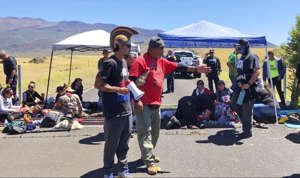 In this July 15, 2019, photo from video, protest leader Kaho'okahi Kanuha, center left, talks to demonstrators, some of whom have chained themselves to a cattle guard on a road at the base of Mauna Kea on Hawaii's Big Island.