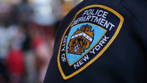 a close up of a hat: NYPD officer doused with water in Harlem