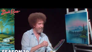 a man looking at a screen: Take a walk with Bob Ross down a little lakeside path in a secluded place; you'll delight in the discovery of a small uninhabited island.   Season 29 of The Joy of Painting with Bob Ross features the following wonderful painting instructions: island in the Wilderness, Autumn Oval, Seasonal Progression, Light at the Summit, Countryside Barn, Mountain Lake Falls, Cypress Creek, Trapper's Cabin, Storm on the Horizon, Pot O' Posies, A Perfect Winter Day, Aurora's Dance, and Woodman's Retreat.  Subscribe to the official Bob Ross YouTube channel - http://bit.ly/BobRossSubscribe  Season 29 Playlist: https://www.youtube.com/playlist?list=PLAEQD0ULngi6c0D5_ELtW5p_NLShDktAN  Originally aired on 8/24/1993