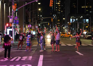 People celebrate on 6th Ave after the lights came back on after a major power outage affecting parts of New York City on July 13, 2019. - Subway stations plunged into darkness and the billboards of Times Square suddenly flicked off as New York's Manhattan was hit by a power outage on Saturday. About 42,000 customers lost electricity in the early evening, according to the Con Edison utility, which did not give a reason for the cut. (Photo by TIMOTHY A. CLARY / AFP)        (Photo credit should read TIMOTHY A. CLARY/AFP/Getty Images)