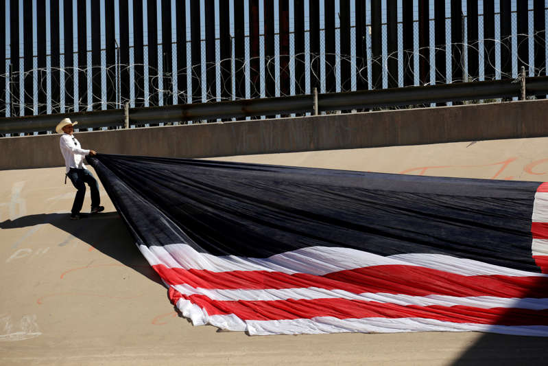 Roberto Marquez, known as Roberz, arranges a large U.S. flag as part of a protest called 'United States of Immigrants'.