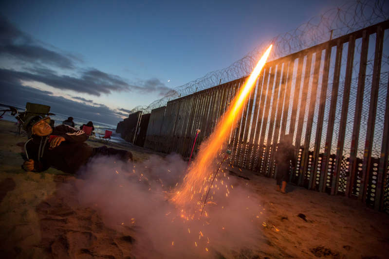 A man lights a firecracker on the border between Mexico and the USA on US Independence Day.