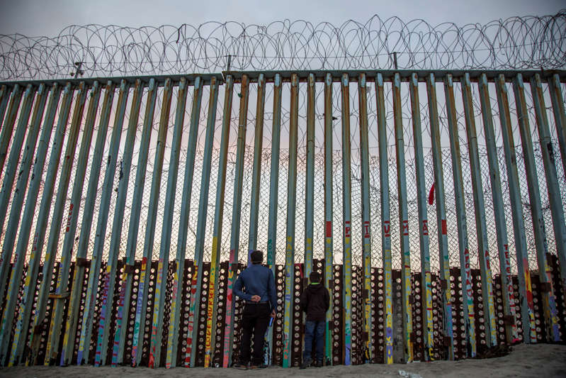 A man and his child look through the border wall in the Mexican city of Tijuana towards the US city of San Diego.