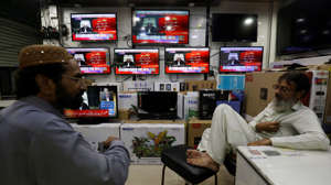 Shopkeepers talk as television screens display the coverage of the World Court review of the death penalty given to former Indian navy commander Kulbhushan Sudhir Jadhav, at a shop in Karachi, Pakistan July 17, 2019. REUTERS/Akhtar Soomro