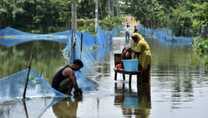 An Indian woman washes clothes next to man cleaning a pot along a flooded road following heavy monsoon rains at Kaljhar village in Barpeta district of India's Assam state on July 17, 2019. - In India, the death toll rose to at least 120 and entire communities were cut off by rising floodwaters which damaged or submerged roads. (Photo by David TALUKDAR / AFP)        (Photo credit should read DAVID TALUKDAR/AFP/Getty Images)