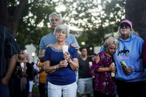 Susan Meyers and husband Michael Oshan listen to a hymn during a vigil for victims of a Sunday evening shooting that left three people dead at the Gilroy Garlic Festival, Monday, July 29, 2019, in Gilroy, Calif.