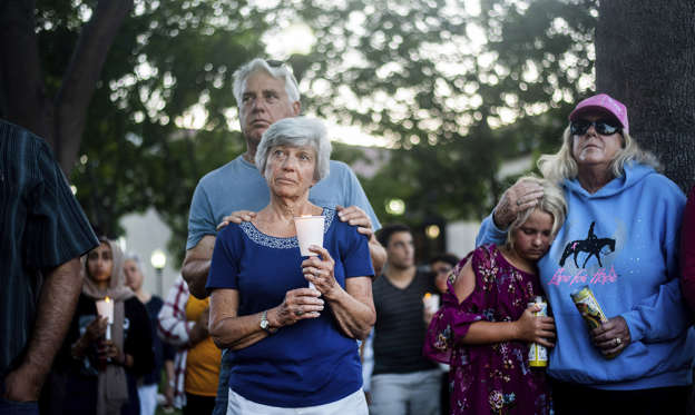 Slide 1 of 45: Susan Meyers and husband Michael Oshan listen to a hymn during a vigil for victims of a Sunday evening shooting that left three people dead at the Gilroy Garlic Festival, Monday, July 29, 2019, in Gilroy, Calif.