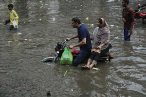 People navigate a flooded street in Lahore, Pakistan, Tuesday, July 30, 2019. Every year, many cities in Pakistan struggle to cope with the annual monsoon deluge, drawing criticism about poor planning. The monsoon season runs from July through September. (AP Photo/K.M. Chaudhry)