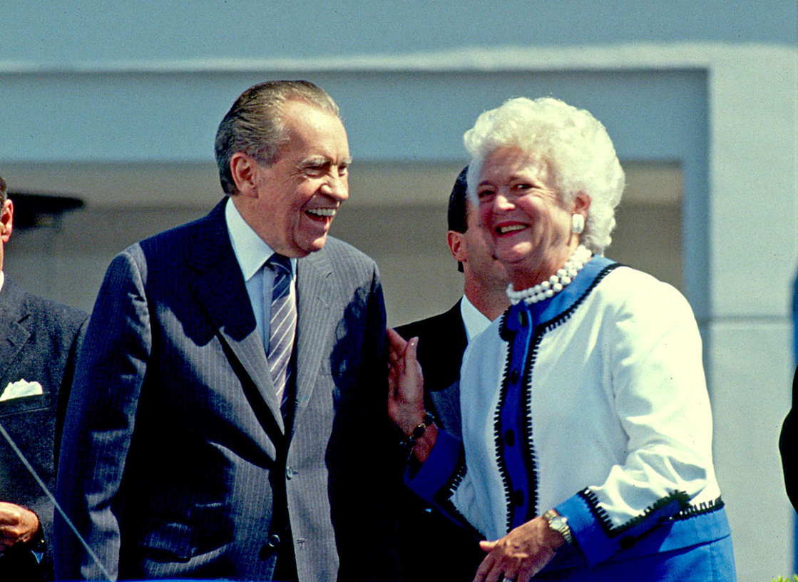 President Richard Nixon enjoys a laugh with Barbara Bush at the opening of The Richard Nixon Library & Birthplace (Photo By Paul Harris/Getty Images)