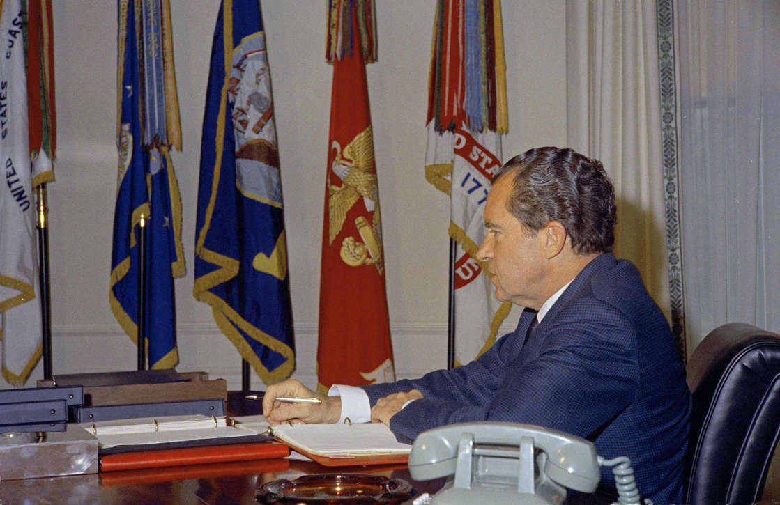 President Richard Nixon works at his desk at the White House in Washington, D.C., preparing for his European trip, Feb. 16, 1969. Military flags decorate his office. (AP Photo)