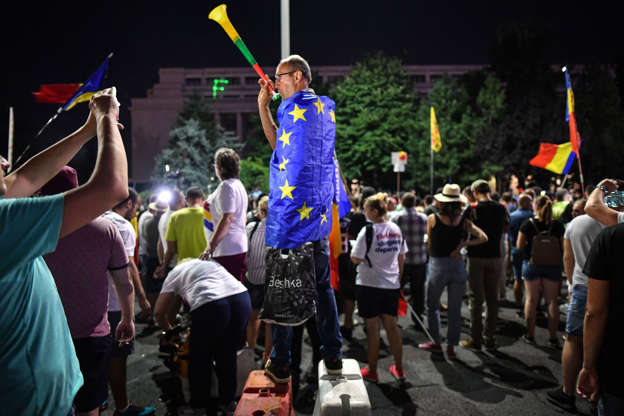 A man wears a European Union flag during a protest against the government and the Social Democratic ruling Party (PSD) in front of the Romanian Government headquarters in Bucharest August 10, 2019. - Around 24,000 protesters marched down the streets of Bucharest to demand the resignation of the left-wing government, one year after a rally violently repressed by the Romanian Gendarmes. (Photo by Daniel MIHAILESCU / AFP)        (Photo credit should read DANIEL MIHAILESCU/AFP/Getty Images)