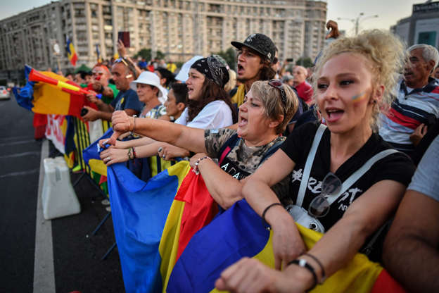 People gesture and shout slogans during a protest against the government and the Social Democratic ruling Party (PSD) in front of the Romanian Government headquarters in Bucharest August 10, 2019. - Around 24,000 protesters marched down the streets of Bucharest to demand the resignation of the left-wing government, one year after a rally violently repressed by the Romanian Gendarmes. (Photo by Daniel MIHAILESCU / AFP)        (Photo credit should read DANIEL MIHAILESCU/AFP/Getty Images)