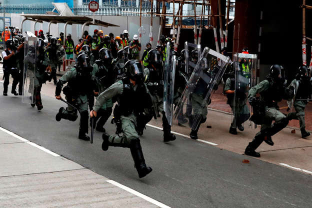 Slide 15 of 71: Riot police run to disperse anti-extradition bill protesters during a protest at Sham Shui Po in Hong Kong, China, August 11, 2019. REUTERS/Tyrone Siu