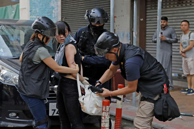 Slide 21 of 71: Riot policemen search a protester's bag during the anti-extradition bill protest in Hong Kong, Sunday, Aug. 11, 2019. Police fired tear gas late Sunday afternoon to try to disperse a demonstration in Hong Kong as protesters took over streets in two parts of the Asian financial capital. (AP Photo/Kin Cheung)