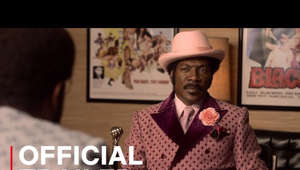 "a man wearing a red hat: Academy Award nominee Eddie Murphy portrays real-life legend Rudy Ray Moore, a comedy and rap pioneer who proved naysayers wrong when his hilarious, obscene, kung-fu fighting alter ego, Dolemite, became a 1970s Blaxploitation phenomenon.  Watch Dolemite Is My Name on Netflix: https://www.netflix.com/title/80182014  SUBSCRIBE: http://bit.ly/29qBUt7  About Netflix: Netflix is the world's leading internet entertainment service with over 151 million paid memberships in over 190 countries enjoying TV series, documentaries and feature films across a wide variety of genres and languages. Members can watch as much as they want, anytime, anywhere, on any internet-connected screen. Members can play, pause and resume watching, all without commercials or commitments.  Connect with Netflix Online: Visit Netflix WEBSITE: http://nflx.it/29BcWb5 Like Netflix Kids on FACEBOOK: http://bit.ly/NetflixFamily Like Netflix on FACEBOOK: http://bit.ly/29kkAtN Follow Netflix on TWITTER: http://bit.ly/29gswqd Follow Netflix on INSTAGRAM: http://bit.ly/29oO4UP Follow Netflix on TUMBLR: http://bit.ly/29kkemT  Dolemite Is My Name | Official Trailer | Netflix http://youtube.com/netflix  When Hollywood shuts him out, multi-talented Rudy Ray Moore strikes out on his own to make the 1975 blaxploitation film ""Dolemite."" Eddie Murphy stars."