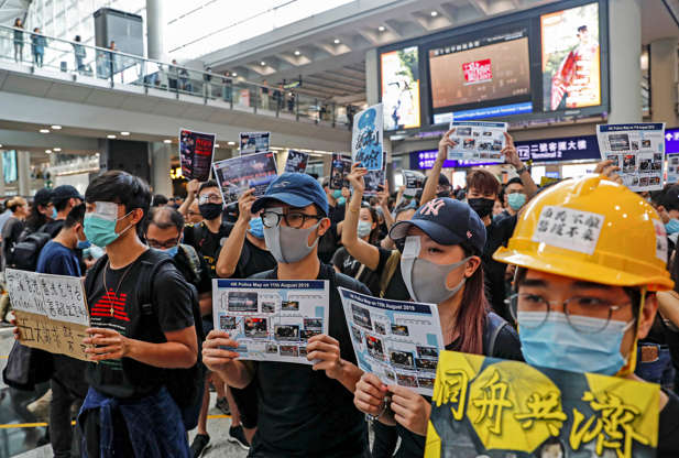 Slide 7 of 71: REFILE - CORRECTING GRAMMAR Anti-extradition bill protesters cover their eyes with gauze during a mass demonstration after a woman was shot in the eye during a protest at Hong Kong International Airport, in Hong Kong, China August 12, 2019.