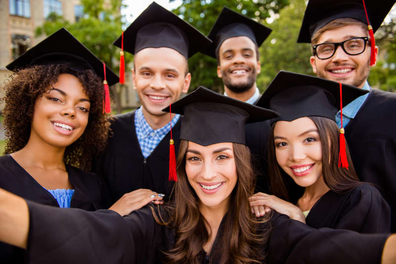 Selfie for memories. Six with cheerful graduates are posing for a selfie shot.