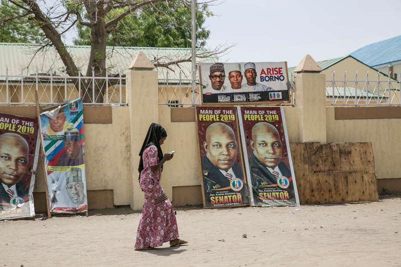 MAIDUGURI, NIGERIA - APRIL 27: A girl looks at her mobile phone while she walks past the political posters that bear the portraits of the Nigerian president, Muhammadu Buhari (top left) and other candidates on April 27, 2019 in Maiduguri, Nigeria. General elections were held in Nigeria on 23 February 2019 to elect the President, Vice President, House of Representatives and the Senate, which the incumbent president Muhammadu Buhari won. In Maiduguri, the capital city of Borno State in northeastern region, saw democracy working by electing the president, governor, and other cabinet members, despite the military tensions with Boko Haram, a Jihadist group which began its military insurgency in 2009. Ten years into the insurgency, the city has become relatively safer than before; however, it still possesses tens of thousands of Internally Displaced Persons of the armed-conflict who could not return their home villages. (Photo by Jean Chung/Getty Images)