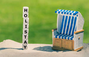 "Holiday at home. Dice form the word ""holistay"" next to a beach chair."