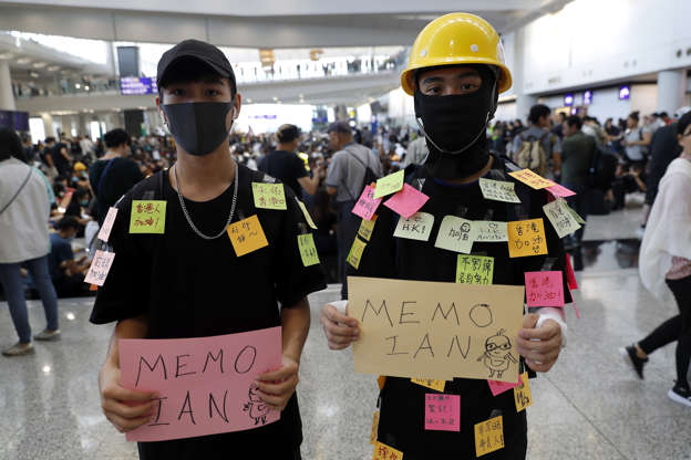 Slide 50 of 71: Protesters hold banners as they demonstrate at the airport In Hong Kong on Friday, Aug. 9, 2019. Pro-democracy protesters held a demonstration at Hong Kong's airport Friday even as the city sought to reassure visitors to the city after several countries issued travel safety warnings related to the increasing levels of violence surrounding the two-month-old protest movement. (AP Photo/Vincent Thian)