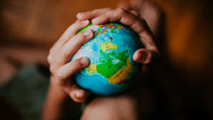 Child's hands holding a globe, space for copy.