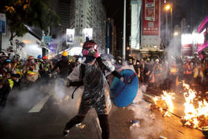 A protestor hurls back an exploded tear gas shell at police officers on Aug. 31.