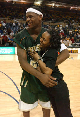 a man holding a microphone: LeBron James celebrates with his mother, Gloria James, Saturday, March 15, 2003, after a win against Ottwa-Glandorf during the Ohio High School Athletic Association Boys' basketball Regional Tournament in Toledo, Ohio.