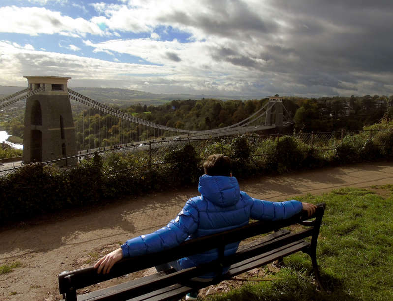 Landscape photo of man in a blue coat sitting on a park bench overlooking the Clifton Suspension Bridge in Bristol, England