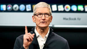 Tim Cook standing in front of a television screen