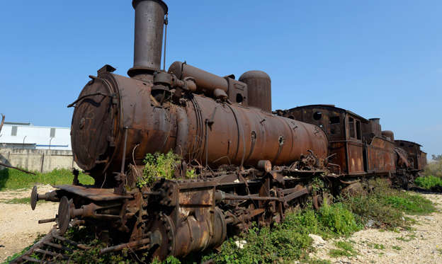幻灯片 15 - 1: A rusted locomotive is seen at the deserted train station in Tripoli, North Lebanon, 23 February 2019 (issued 24 February 2019). The Tripoli railway station began operating in 1911 and was connected to the Syrian city, Homs, with a single track. It formed the terminus of the Orient Express line in the twenties, thirties and forties of the last century. Tripoli station was connected to the central station of Beirut (Mar Mikael) in 1945. In 1975, the station was abandoned and now contains a number of multipurpose buildings. These buildings were severely damaged during the civil war (1975?1991). A series of ancient multi-purpose wagons, two German G7 class locomotives made in 1895, and four German G8 locomotives, made in 1901 and 1906 remain on the site.