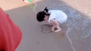 Little girl refuses to give up as waves keep washing away her message