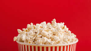 Popcorn in classic striped bukcet on red background. Fluffy maise paper box, copy space. Fast food and movie snack, entertainment concept