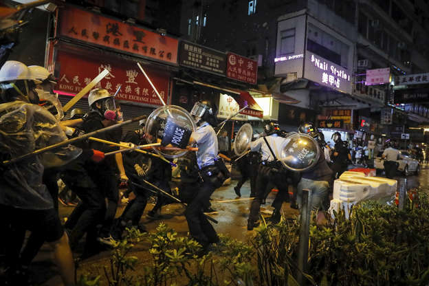 Slide 1 of 50: Policemen clash with demonstrators on a street during a protest in Hong Kong, on Aug. 25.