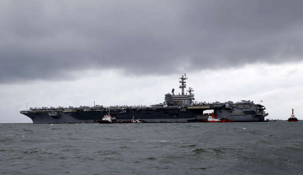 FILE - In this Aug. 7, 2019, file photo, rain clouds loom over the U.S. aircraft carrier USS Ronald Reagan as it is anchored off Manila Bay, Philippines for a port call. USS Ronald Reagan sailed through the disputed South China Sea in the latest show of America's military might amid new territorial flare-ups involving China and three rival claimant states. (AP Photo/Bullit Marquez, File)