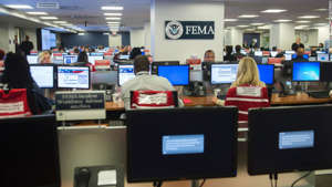 a desktop computer sitting on top of a desk: Employees work on computers inside the FEMA Command Center at Federal Emergency Management Agency Headquarters in Washington, DC, August 4, 2017. / AFP PHOTO / SAUL LOEB        (Photo credit should read SAUL LOEB/AFP/Getty Images)