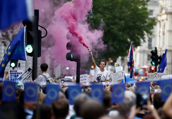 Slide 2 of 54: An anti-Brexit protestor releases colored smoke, outside the Houses of Parliament in London, Britain August 28, 2019. REUTERS/Henry Nicholls TPX IMAGES OF THE DAY