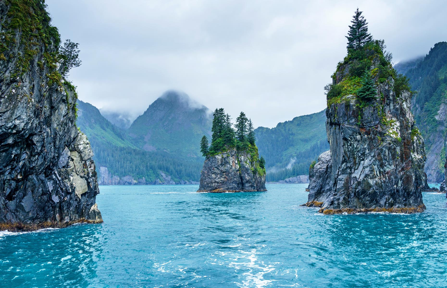 Slide 36 of 61: At a quick glance, this bay, with its blue waters and sea stacks, could be in Southeast Asia – instead it's actually the chillier waters of Alaska's Kenai Fjords National Park. The product of millennia of erosion, these sea stacks can be found peppered across the park, from Aialik Bay to the craggy Chiswell Islands. They're home to seabirds such as cormorants and puffins, plus the park's resident bats. The best way to take them in is from a kayak on the water.