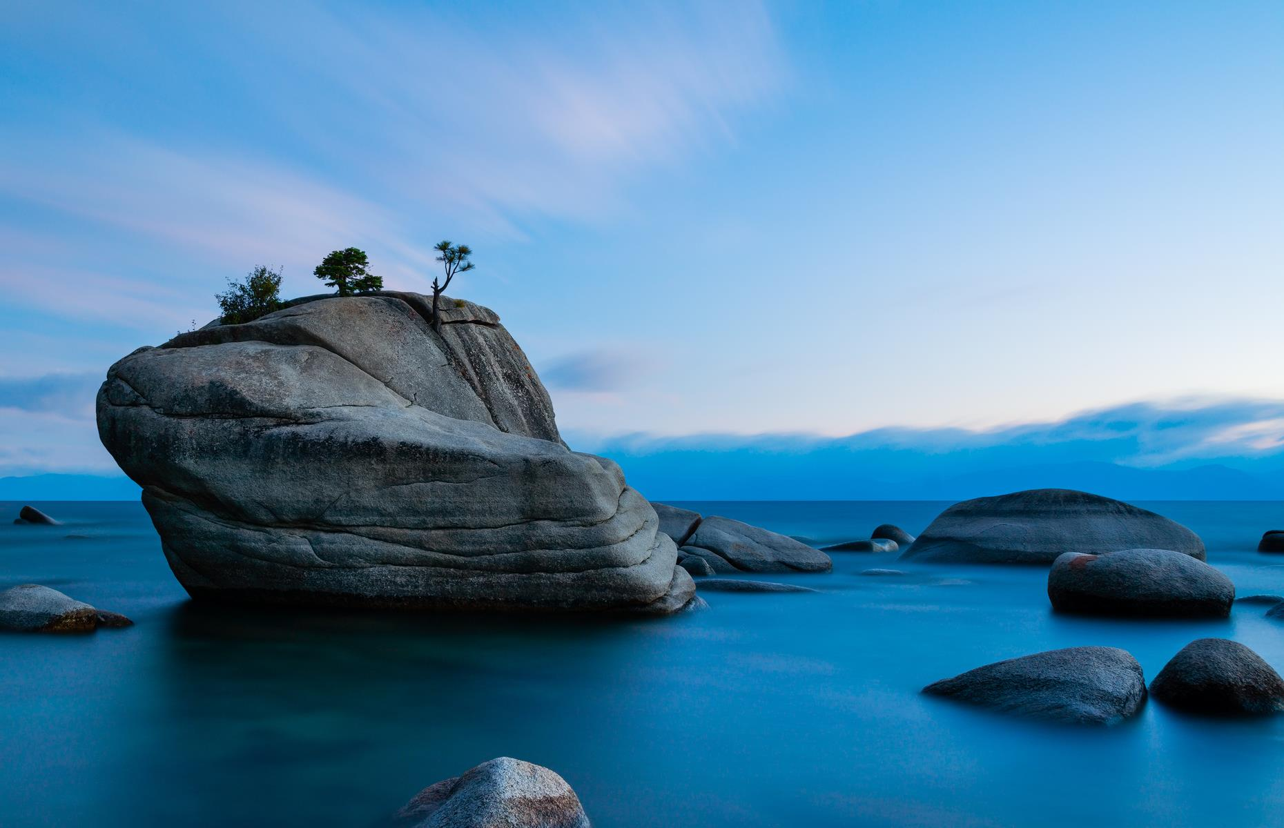 Slide 15 of 61: The perfect subject for keen photographers, Bonsai Rock is an eye-catching crag on the Nevada portion of Lake Tahoe. Four little trees sprout from the hulking rock and it's reached by a brief but steep hike towards the waters. Come at sunrise or sunset for spectacular shots, and remain after dark to see the clear skies filled with stars.
