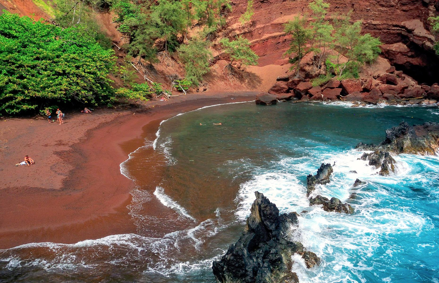 Slide 46 of 61: Also known as Kaihalulu Beach, this rust-colored strand on Maui is gloriously secluded, its sand contrasting with the bright blue waters lapping at the shore. The ruddy hue is the result of the ever-eroding volcano that backs the crescent. The beach can be reached via a steep, narrow trail (note that many consider the trail dangerous, hence the beach's relative seclusion), and there are no facilities, so come prepared.
