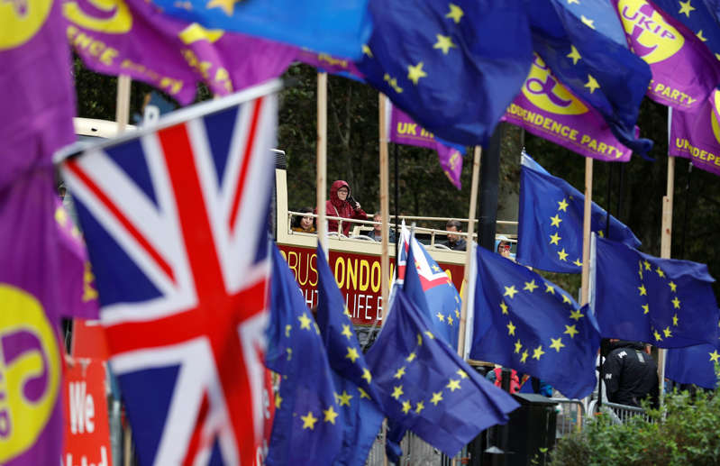 A tourist double-decker bus drives past flags hanged by pro-Brexit and anti-Brexit demonstrators outside the Houses of Parliament in Westminster in London, Britain, September 9, 2019. REUTERS/Peter Nicholls