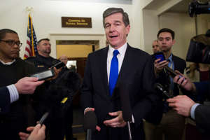 North Carolina Gov. Roy Cooper speaks with reporters after testifying before the House Natural Resources Committee hearing on climate change on Capitol Hill in Washington, Wednesday, Feb. 6, 2019. (AP Photo/Cliff Owen)