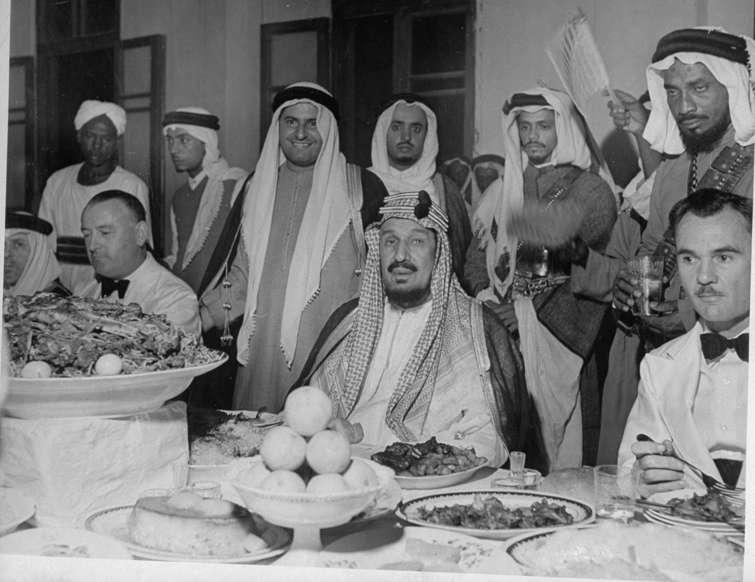 الشريحة 10 من 14: King Ibn Saud (C) eating at dinner table.  (Photo by John Phillips/The LIFE Picture Collection/Getty Images)