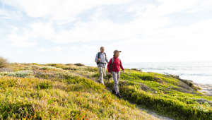 Senior couple (aged 65-69) hiking together on a coastal path