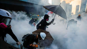 Anti-government protesters protect themselves with umbrellas among tear gas during a demonstration near Central Government Complex in Hong Kong, China, September 15, 2019. REUTERS/Jorge Silva