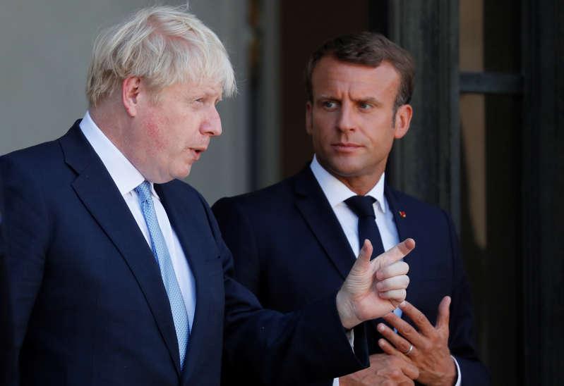French President Emmanuel Macron accompanies British Prime Minister Boris Johnson