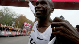Marathon runner Eliud Kipchoge from Kenya points to the clock after crossing the finish line of the INEOS 1:59 Challenge after 1:59:40 in Vienna, Austria, Saturday, Oct. 12, 2019. He is the first human ever to run a marathon under two hours. (AP Photo/Ronald Zak)