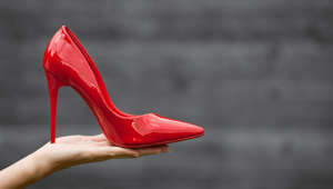 Red high heel in girl's hand.