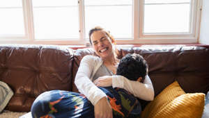 Happy, carefree mother cuddling with son on living room sofa